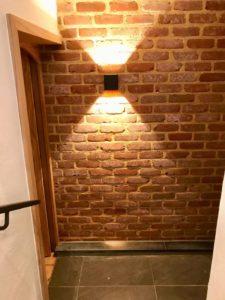 Une applique noire sur mur en briques rouges pour un éclairage d'ambiance chaleureux.