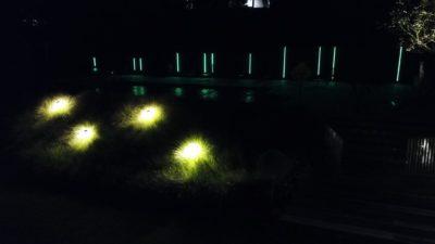 Profilés pour lampes à LED placés verticalement dans un jardin.
