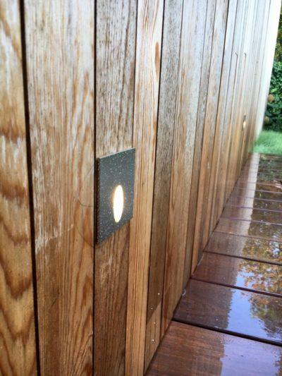 Spots biseautés à 70% sur bardage pour éclairer le chemin du jardin.