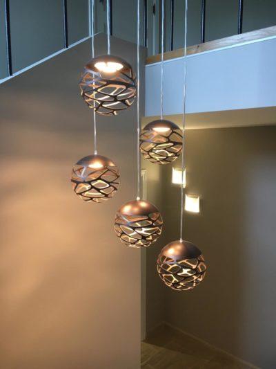 Un lustre Studio Italia avec cinq boules en couleur bronze pour une lumière chaude dans toute la cage d'escalier.