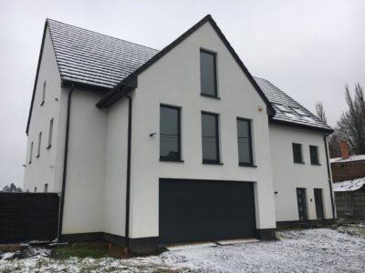 Façade blanche et éclairage extérieur d'une maison passive.