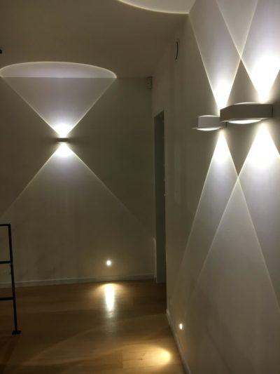 éclairage intérieur d'un couloir avec appliques murales et balises intégrées.